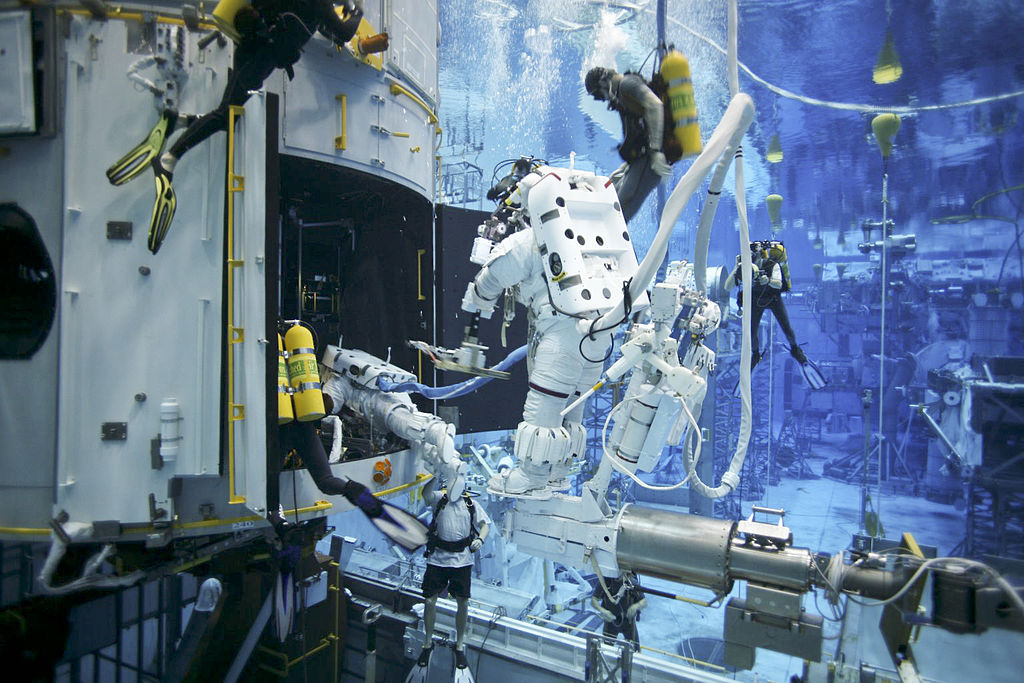 Servicing Mission 4 astronauts practice on a Hubble model underwater at the Neutral Buoyancy Lab in Houston under the watchful eyes of NASA engineers and safety divers