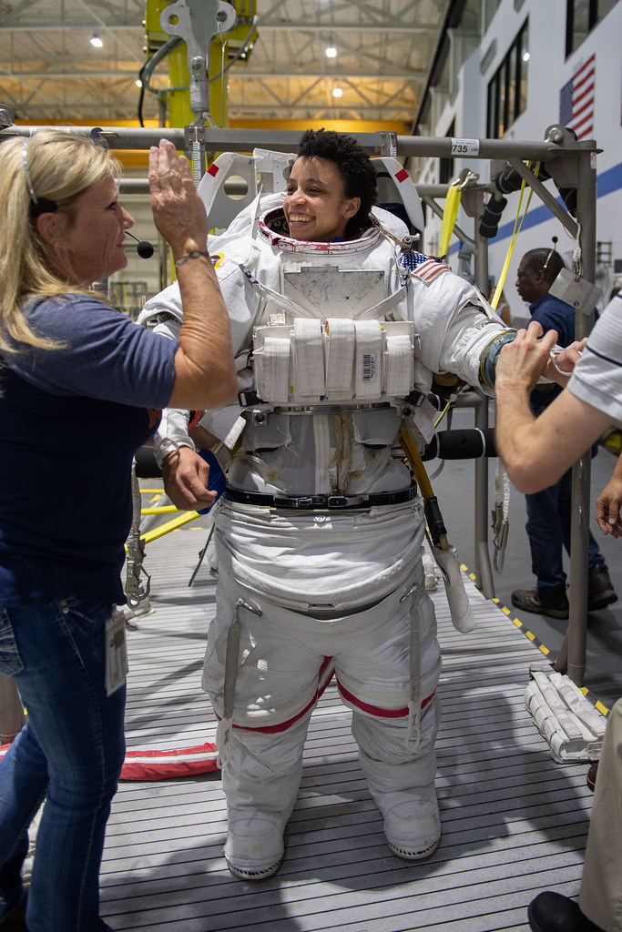 (05-22-19) --- 2017 NASA astronaut candidate Jessica Watkins is helped into a spacesuit prior to underwater spacewalk training at NASA Johnson Space Center's Neutral Buoyancy Laboratory in Houston. Photo Credit: (NASA/David DeHoyos)