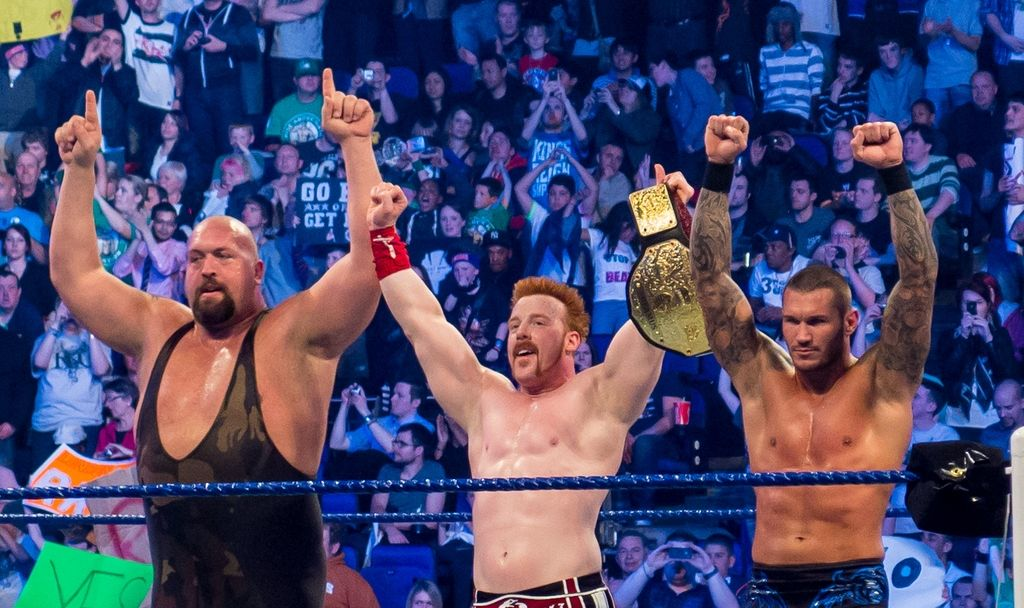Three professional wrestlers raise their arms before a crowd.