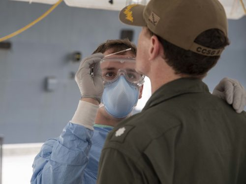 U.S. Navy Hospital Corpsman takes a sample of a Sailor embarked aboard the aircraft carrier USS Theodore Roosevelt to be tested for COVID-19 April 20, 2020.