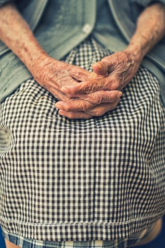 Shot of an old woman's hands folded in her lap.