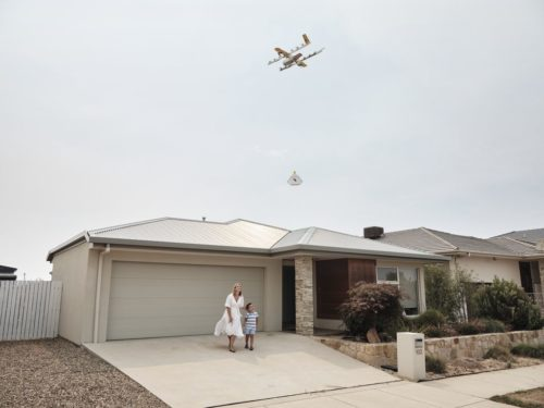 Wing drone with package in the air.