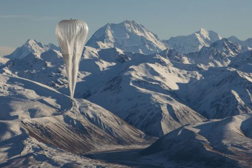 A Loon balloon is seen over mountains.