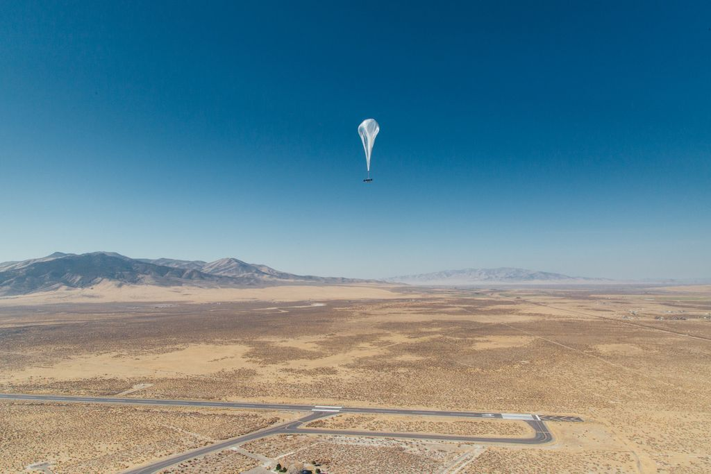 A Loon balloon is seen over a wide open landscape.