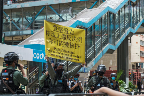 Police held up banners warning the protesters that they could now be arrested based on the signs the held up or the words they shouted or sang.