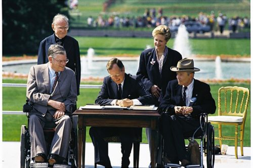 President George H. W. Bush signs the Americans with Disabilities Act of 1990 into law. Pictured (left to right): Evan Kemp, Rev Harold Wilke, Pres. Bush, Sandra Parrino, Justin Dart.