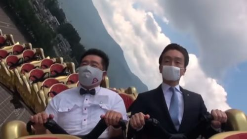 Two men in business suits ride a Fuji-Q Highland rollercoaster with serious expressions.