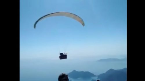 View of Hasan Kaval's couch flying, suspended from a paraglider.