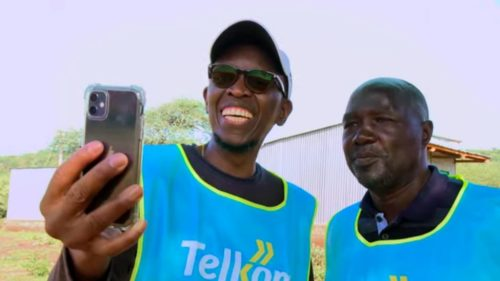 People from Telkom Kenya look at a cell phone getting service from a Loon balloon.