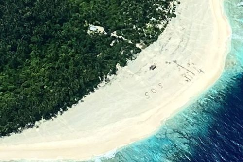 Aerial view of SOS on beach in Micronesia.