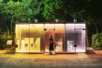 A woman enters transparent toilets designed by Shigeru Ban at night.