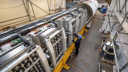 Engineers slide racks of Microsoft servers and associated cooling system infrastructure into Project Natick's Northern Isles datacenter at a Naval Group facility in Brest, France.