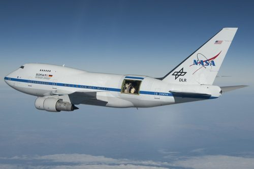 NASA's SOFIA Flying Infrared Observatory - an airplane flying through the sky with an observation port open near the tail.