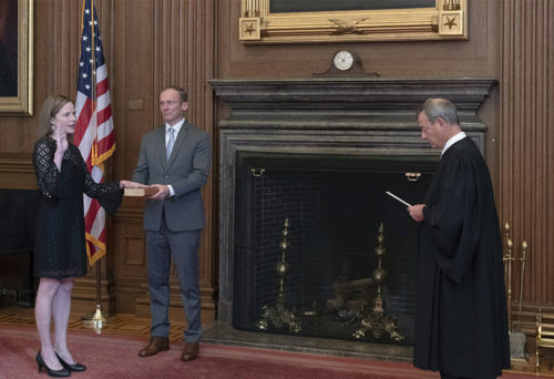 Chief Justice John G. Roberts, Jr., administers the Judicial Oath to Judge Amy Coney Barrett in the East Conference Room, Supreme Court Building. Judge Barrett's husband, Jesse M. Barrett, holds the Bible.Credit: Fred Schilling, Collection of the Supreme Court of the United States