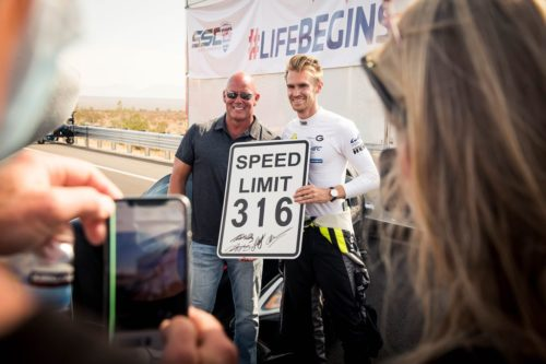 "SSC leader Jerod Shelby (left)  and driver Oliver Webb (right), holding a sign saying, ""Speed Limit 316""."