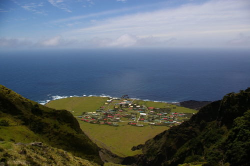 View looking from high on Tristan de Cunha, past houses out to the sea.