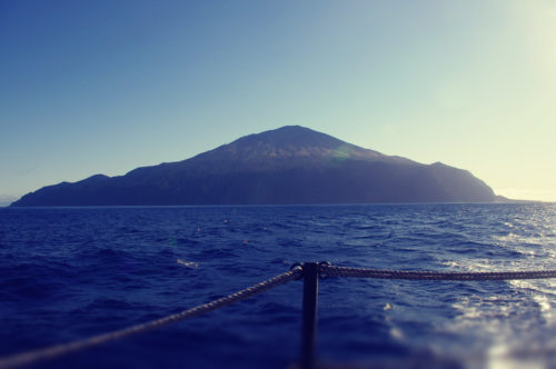 The island of Tristan da Cunha seen from a boat on the sea. The boat's rope railing is visible in the foreground.