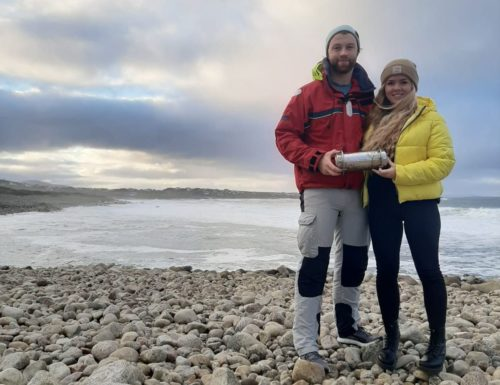 Conor McClory and Sophie Curran standing on a beach holding the time capsule.