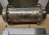 Closeup of the time capsule and a ruler, showing that its about 10 inches 25 centimeters) long.