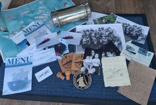 Items from the time capsule spread out, including a map, menus, photographs, postcards, and letters..