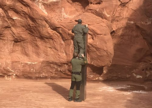 A worker stands on another worker's shoulders to look at the top of the metal monolith found in the Utah desert.