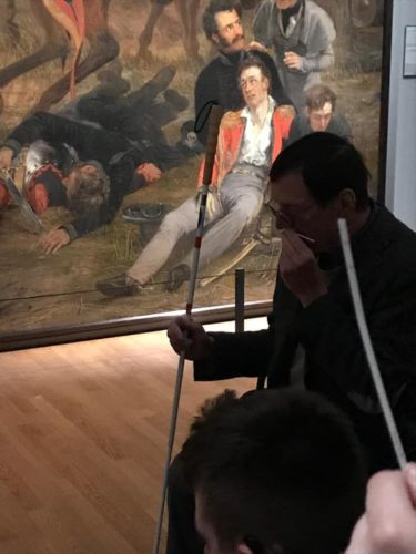 A man with a white cane seated in front of a painting sniffs a scented cardboard strip. In the foreground, another strip is visible, close up. Hannes walrafen smell tour for the blind at Rijksmuseum.