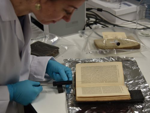 The smell of an old book is being extracted in the Heritage Science Lab at UCL. A gloved-handed scientist pulls a plunger from a tube pointed at an old book that is lying open.