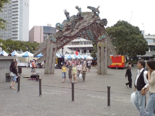 Wahanui (entry gate) by Māori sculptor and painter Selwyn Muru forms a symbolic entrance to Aotea Square in Auckland City, New Zealand, seen here on a market Saturday. Looking towards the west into the square from Queen Street.