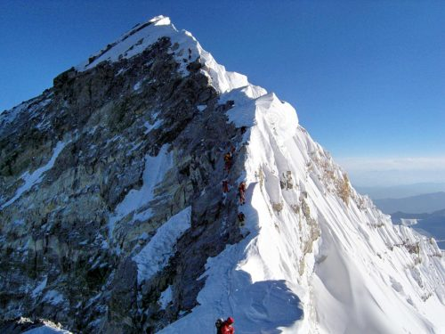 View upward along the southeastern ridgeline, the Hillary Step is visible. The top of the South-West face is on the left in shadow, and in the light to the right is the top of the East/Kangshung face.