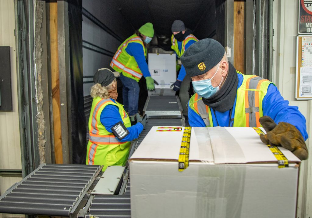 UPS workers load boxes of the Pfizer coronavirus vaccine to be shipped.