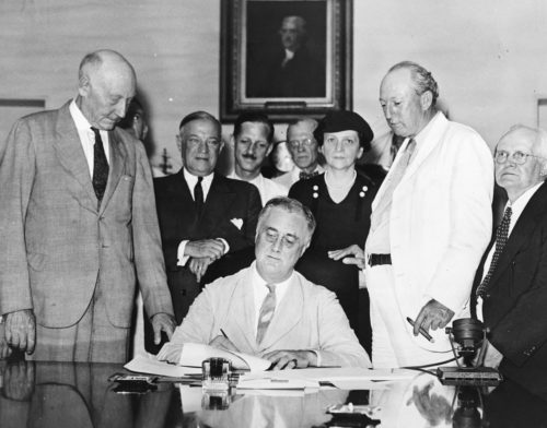 President Roosevelt signs Social Security Act as several politicians, including Frances Perkins, look on.