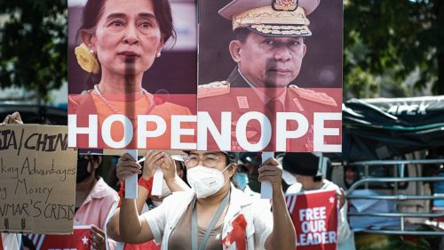 Protest in Myanmar against Military Coup 14-Feb-2021 - protester holding sign with images of Aung San Suu Kyi marked 'hope' and General Min Aung Hlaing, marked 'nope'.