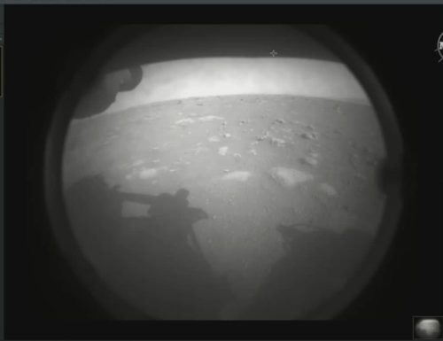 This is the first image NASA's Perseverance rover sent back after touching down on Mars on Feb. 18, 2021. The view, from one of Perseverance's Hazard Cameras, is partially obscured by a dust cover. A grey-scale image of a dusty, rocky Mars surface, with the shadow of the Perseverance Rover seen in the foreground.