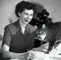 Black and white image of Beverly Cleary, around 1955. She's smiling at the camera while appearing to edit a typewritten manuscript with a pencil. A cat is beginning to walk across the manuscript.