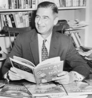 Ted Geisel (Dr. Seuss) half-length portrait, seated at desk covered with his books / World Telegram & Sun photo by Al Ravenna.