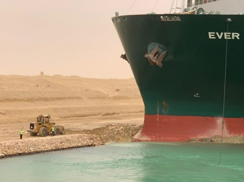 Bulldozer on shore in front of the mega container ship Ever Given.