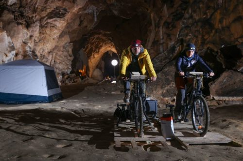 Two Deep Time campers pedal on bikes to generate electricity for lights in the Lombrives cave.
