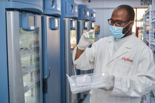 A pharmacist looks at a bottle of AstraZeneca vaccine.