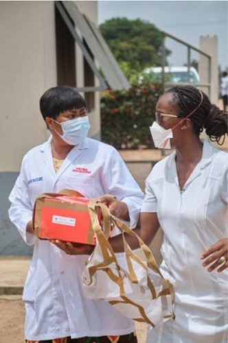 Medical workers collect a package dropped by a Zipline drone.
