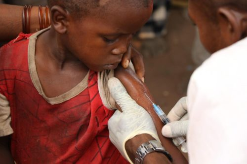 A young child looks on as he is given a vaccination.