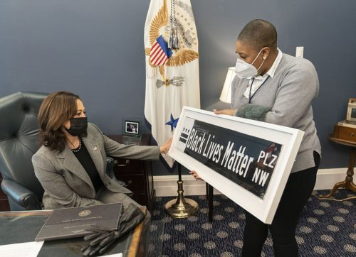 Chief Spokesperson for the Vice President Symone Sanders shows Vice President Kamala Harris a Black Lives Matter street sign Tuesday, Feb. 16, 2021, in her West Wing Office of the White House. The sign is a gift from DC Mayor Muriel Bowser. (Official White House Photo by Lawrence Jackson)