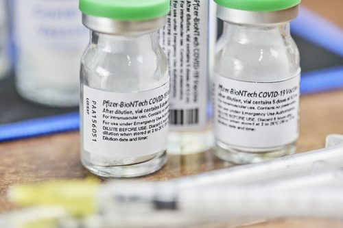 Closeup of two glass vials of Pfizer/BioNTech vaccine.