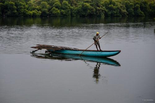 A fisherman maneuvers his boat in the Negombo Lagoon, Negombo, Sri Lanka