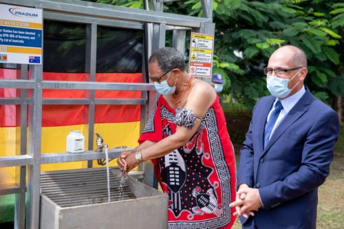 eSwatini's acting Prime Minister Themba Masuku washes his hands at a solar hot water station in Lobamba, eSwatini while Robert Frazer, head of Frazer Solar, looks on.