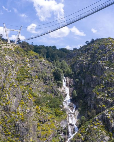 The 516 Arouca bridge in Portugal's Arouca Geopark. View from below, with waterfall in background.