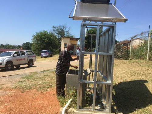 A man washes his hands at a new solar hot water station at a health clinic in eSwatini.