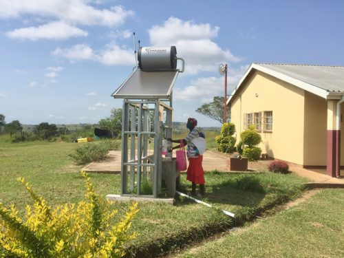 A woman with a baby washes her hands at a new solar hot water station at a health clinic in eSwatini.
