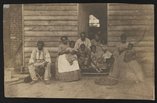 Family of slaves i n front of a simple shack at the Gaines' house in Virginia around 1862.