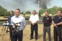 Bill Synder, VP of Operations for Lubrizol speaks to reporters about the Chemtool fire in Rockton, with smoke rising in the background.