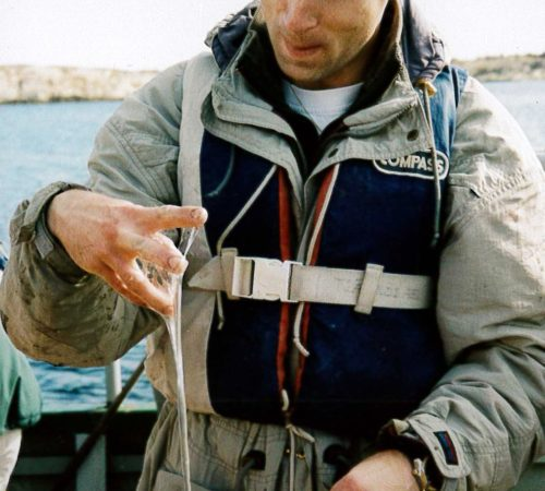 A man with sea snot dripping from one of his hands.